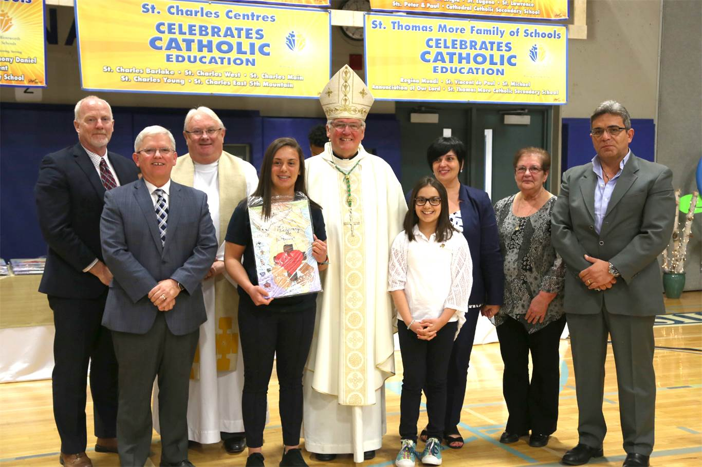 The artwork for this year's Catholic Education Week poster was created by Angela Guglielmo, a Grade 8 student at St. Mark Catholic Elementary School. Pictured, left to right, are: Director of Education David Hansen; Chairperson Patrick Daly; Vicar of Education for the Diocese of Hamilton, Rev. Fr. Con O'Mahony; Angela; The Most Rev. Douglas Crosby, OMI, Bishop of Hamilton; and Angela's family members, sister Antonia, mom Caroline, Nonna Pina, and father Mike. Photo by Jenna Madalena.